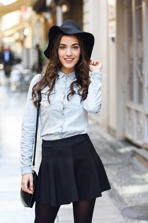 Foto de Portrait of young woman in urban background wearing casual clothes and hat  carrying a bag - Imagen libre de derechos