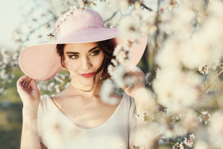 Portrait of young woman in the flowered field in the spring time. Almond flowers blossoms. Girl wearing white dress and pink sun hatの写真素材