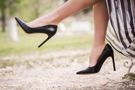 Photo pour Black high heels on the feet of a young woman in a park - image libre de droit