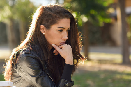 Thoughtful woman sitting alone outdoors. Girl worried in an urban park