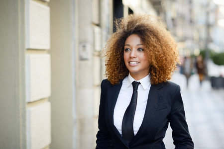 Foto de Portrait of beautiful black businesswoman wearing suit and tie smiling in urban background. Woman with afro hairstyle. - Imagen libre de derechos