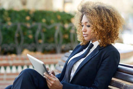 Photo pour Beautiful black curly hair african woman using tablet computer on an urban bench. Businesswoman wearing suit with trousers and tie, afro hairstyle. - image libre de droit