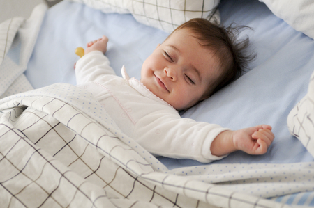 Foto de Smiling baby girl lying on a bed sleeping on blue sheets - Imagen libre de derechos