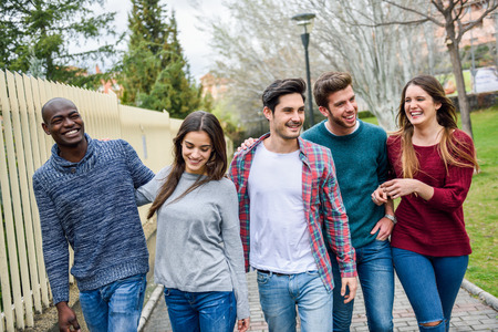 Foto de Group of multi-ethnic young people having fun together outdoors in urban background - Imagen libre de derechos