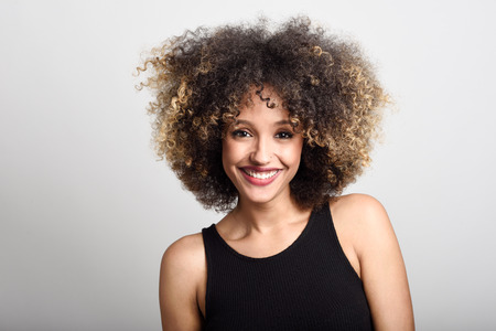 Photo pour Young black woman with afro hairstyle smiling. Girl wearing black dress. Studio shot. - image libre de droit