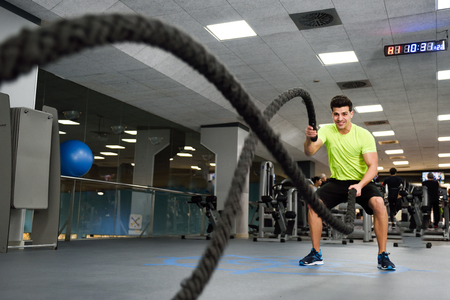Foto de Man with battle ropes exercise in the fitness gym. Young male wearing sportswear. - Imagen libre de derechos