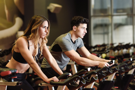 Photo for Two people biking in the gym, exercising legs doing cardio workout cycling bikes. Couple in a spinning class wearing sportswear. - Royalty Free Image