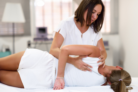 Photo for Professional female physiotherapist giving shoulder massage to blonde woman in hospital. Medical check at the shoulder in a physiotherapy center. - Royalty Free Image