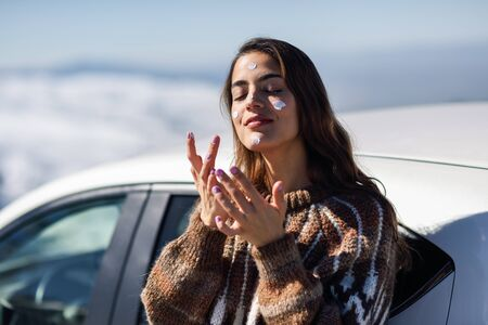 Photo pour Young woman applying sunscreen on her face in snow landscape - image libre de droit