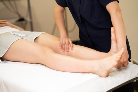 Photo pour Female Physiotherapist inspecting her patient. Medical check in a physiotherapy center. - image libre de droit