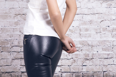 Back view of a woman wearing leather trousers and a white shirt, over a white brick wall.