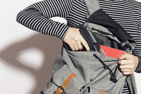 Photo pour Girl hiding a gun in her school backpack. Concealed carry weapon for protection themselves concept. Indoors, over a white wall. - image libre de droit