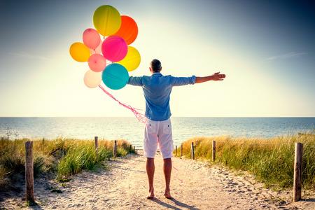 Photo pour happy carefree male looking horizon ocean from dune - image libre de droit