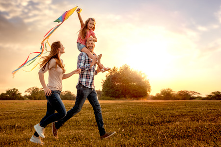 Photo pour family running through field letting kite fly - image libre de droit