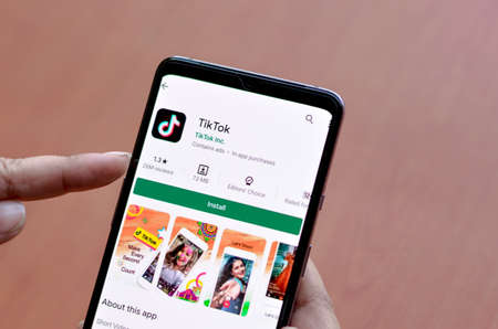 Photo for New Delhi, India, 2020. Woman installing TikTok mobile app on a smartphone screen with a wooden background depicting logo of popular fast growing social network site, showing the low rating - Royalty Free Image