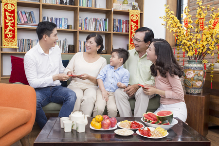 Photo pour Asian family lunar new year at home with yellow apricot flower in the background - image libre de droit
