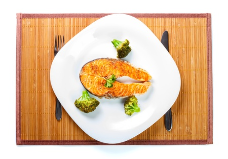 Served salmon meat with delicious broccoli on white plate.