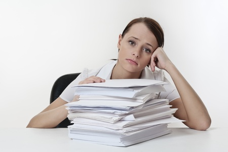 Photo pour A stressed female, sitting at her desk with a large pile of papers stack in front of her  - image libre de droit