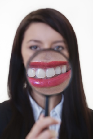 woman holding a magnifying glass over her mouth to show of  crocodile smile