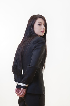 woman dressed in a business suit with her hand tied up behind her back
