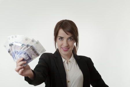 Portrait of happy business woman holding fanned english banknotes