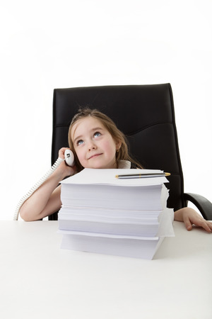 young small girl pretending she's working in a office answering the phone with a large pile of paper work infront of her