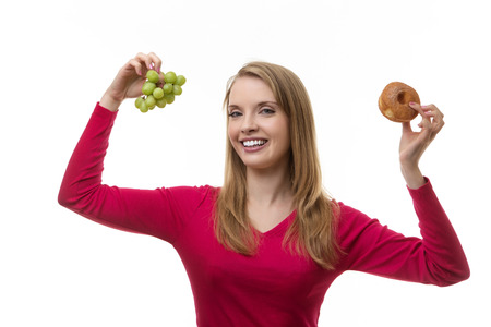 woman holding up grapes and a sugar ring doughnut not sure what to eat