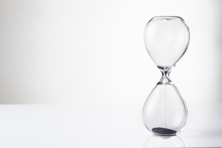 large hour glass sand timer with very little sand in there, time runs our quickly