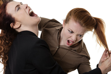 two business woman fighting each other at work