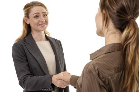 Photo pour Two business woman shaking hands together - image libre de droit