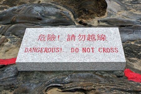 Photo for Chinese and English Stone Sign 'Dangerous! Do Not Cross' - Royalty Free Image