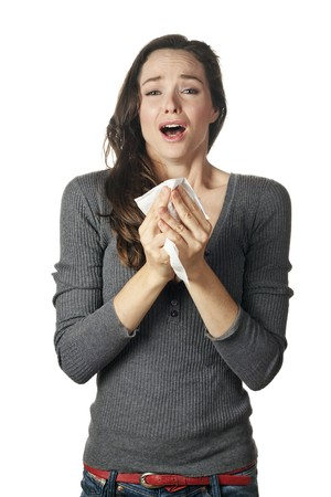 An attractive woman with hay fever or a cold sneezing into tissue