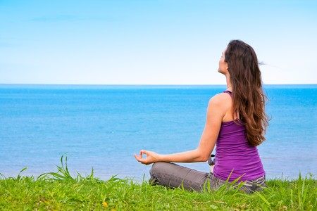Foto de A beautiful young woman sitting meditating with a view of the ocean - Imagen libre de derechos