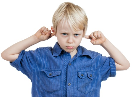 A grumpy cute young boy covers his ears with his fingers  Isolated on white