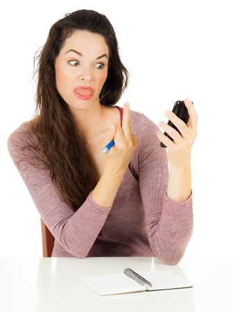 An angry woman is giving her mobile phone the finger  Isolated on white