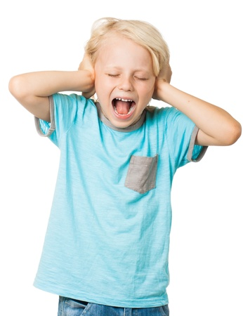 A young distressed young boy screams with his eyes shut and covers his ears with his hands  Isolated on white