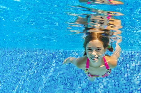 Happy active child swims underwater in pool, beautiful healthy girl swimming and having fun on family summer vacation, kids sport concept