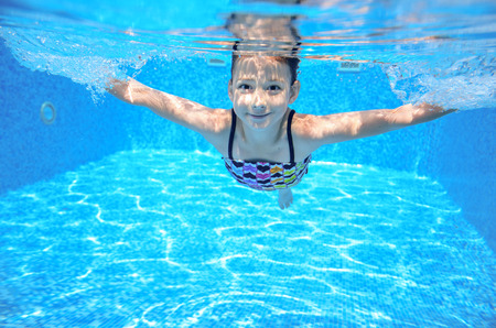 Photo for Happy active underwater child swims in pool, beautiful healthy girl swimming and having fun on family summer vacation, kids sport - Royalty Free Image