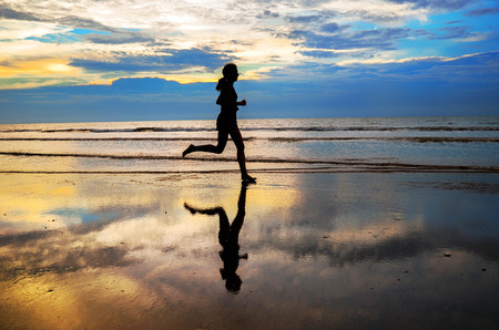 Photo pour Silhouette of woman jogger running on sunset beach with reflection, fitness and healthy life concept - image libre de droit