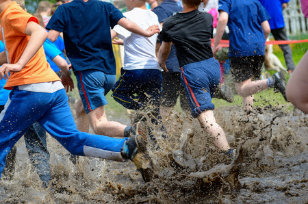 Kids running trail race legs in mud and water
