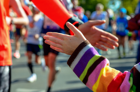 Foto de Blurred background: marathon running race, support runners on road, child's hand giving highfive, sport concept - Imagen libre de derechos