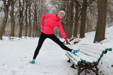 Winter running in park: happy woman runner warming up and exercising before jogging in snow, outdoor sport and fitness concept