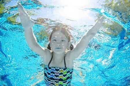 Photo pour Child swims underwater in swimming pool, happy active teenager girl dives and has fun under water, kid fitness and sport on family vacation on resort - image libre de droit