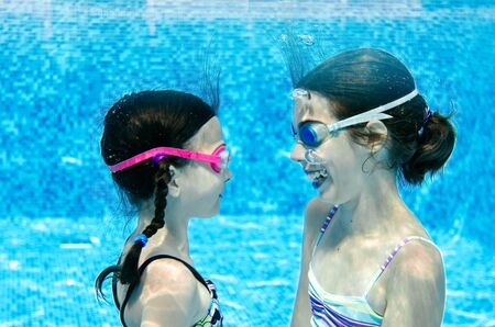 Photo pour Children swim underwater in swimming pool, happy active girls have fun under water, kids fitness and sport on active family vacation - image libre de droit