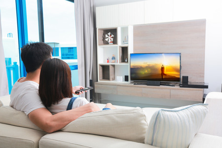Photo pour Happy family watches television while sitting on the sofa. - image libre de droit
