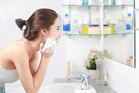 Photo for Woman happy cleanses the skin with foam in bathroom. - Royalty Free Image
