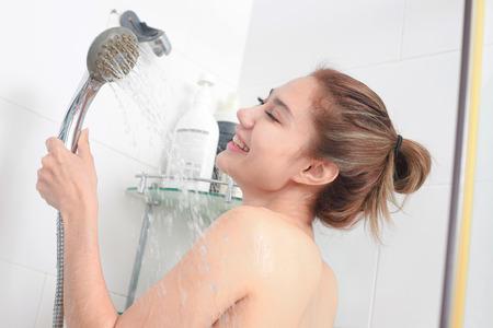 Photo pour Woman taking a shower enjoying water splashing on her. - image libre de droit