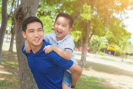 Photo pour Portrait of a father carrying young boy on back at the park  - image libre de droit