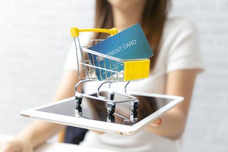 Photo pour Businesswomen holding shopping cart contains credit card on tablet. - image libre de droit