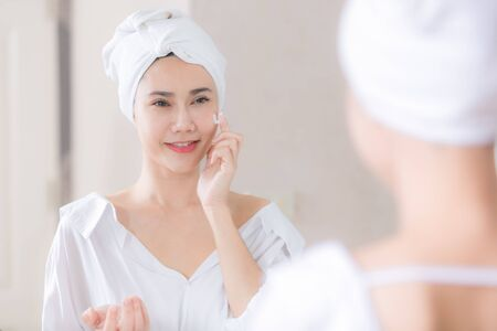 Photo pour Young asian woman applying foundation or moisturizer on her face in front of mirror. - image libre de droit
